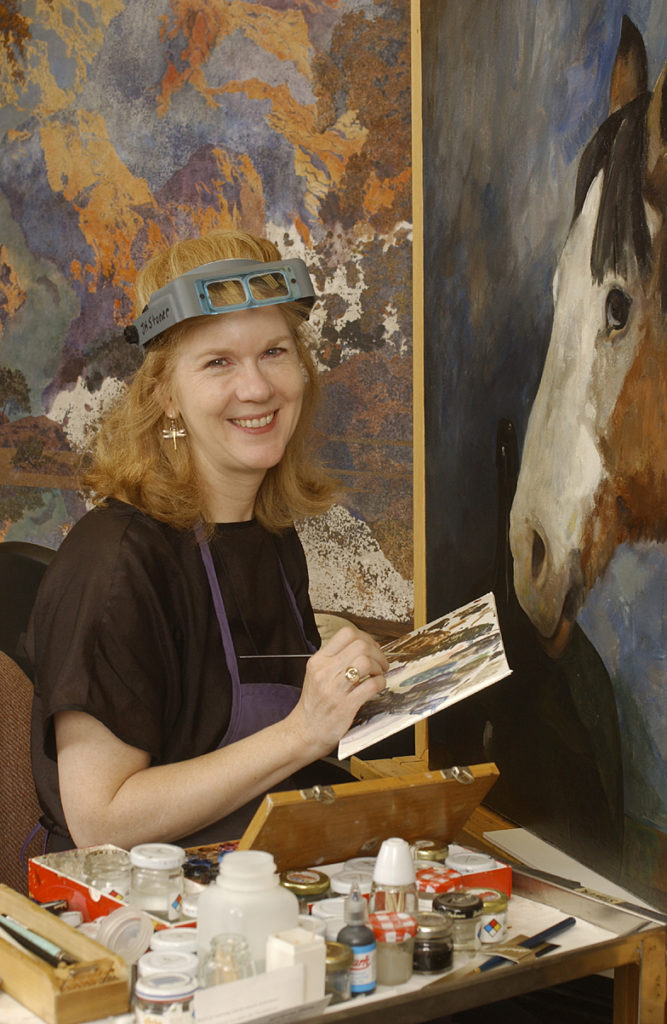 U of D Prof. Joyce Hill-Stoner, art conservation, in her studio at Winterthur Museum. behind her is a Maxfield Parrish (L) and a Jaimie Wyeth (Rt)
